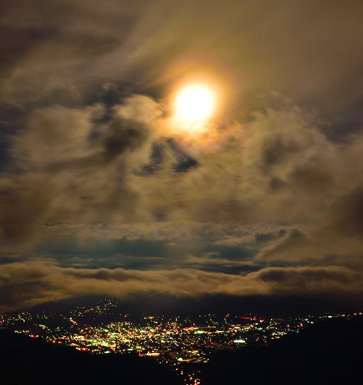 雲間の満月に照らされた夜景