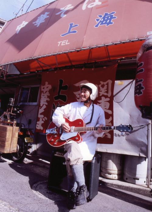 軒先でギターを弾く中華料理屋の主人