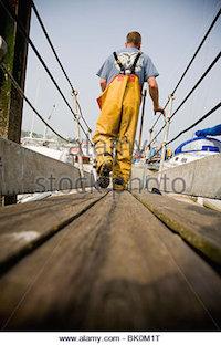 fisherman-wearing-protective-clothing-walking-on-marina-boardwalk-bk0m1t.jpg