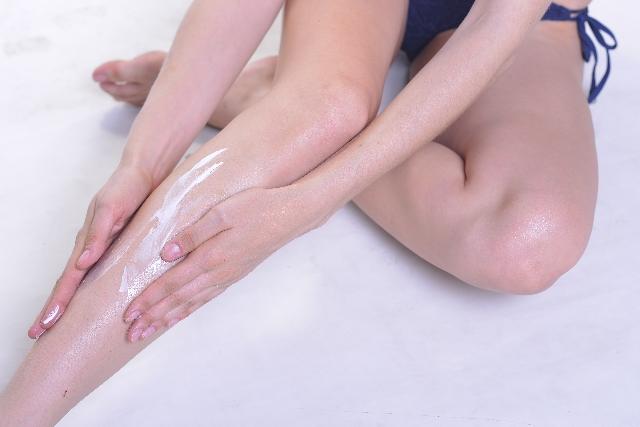 脚に日焼け止めを塗っている女性