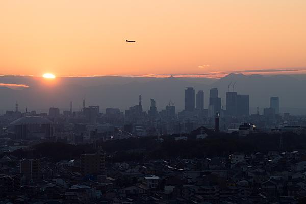 名古屋駅ビルと夕陽と飛行機