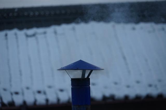 陣笠煙突から立ち上る煙と雪