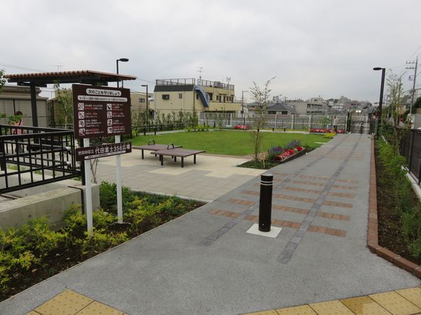 坑口真上に完成した代田富士356広場。地面に線路を模したタイルが埋め込まれている。奥に梅ヶ丘駅を発車した列車のヘッドライトが見える。