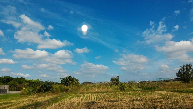 富士見の収穫後の稲株と雲と太陽