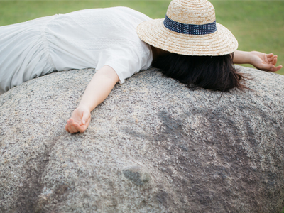 フリー素材 PAKUTASO 石の上のグッタリ女性
