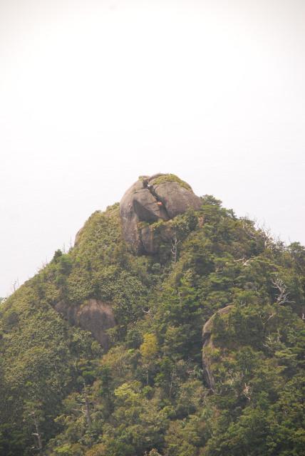 モッチョム岳の山頂_丸い岩の割れ目を人が登っている