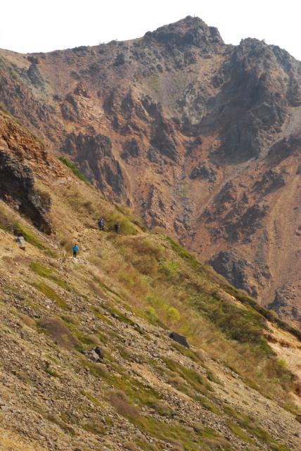 朝日岳の大岩壁を見上げながら登山道を進む