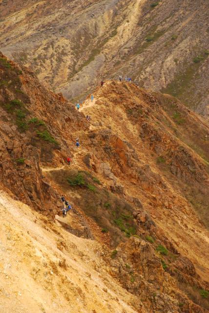 狭い岩の稜線を登山者が列をなして進む